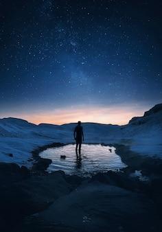 Il viaggiatore si trova in una primavera calda segreta di notte in islanda sotto il cielo stellato mozzafiato con th
