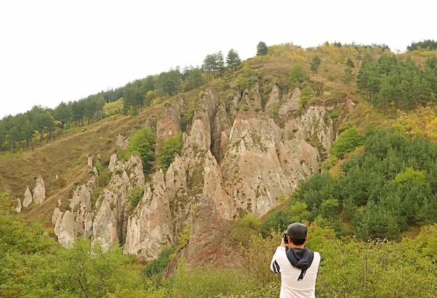 Viaggiatore che scatta foto di fantastiche formazioni rocciose nel vecchio villaggio di grotte di khndzoresk a syunik armenia
