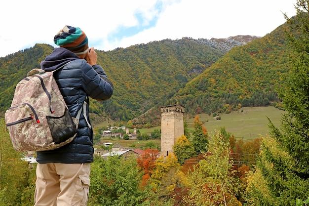 Viaggiatore che fotografa la città di mestia con la torre svan tra le bellissime foglie autunnali della georgia