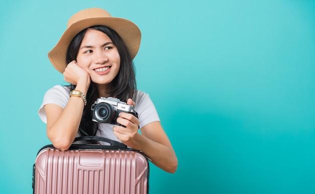 Turista del viaggiatore di bella giovane donna asiatica che tiene la borsa della valigia e la macchina fotografica mirrorless della foto