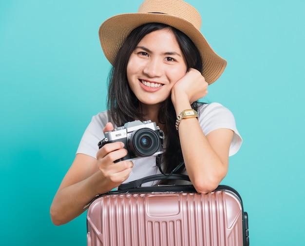 Le vacanze asiatiche felici della bella giovane donna del turista del viaggiatore viaggiano la borsa della valigia della tenuta e la macchina fotografica mirrorless della foto