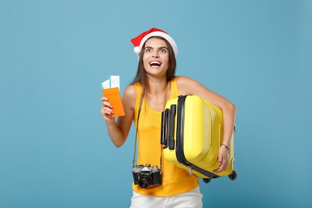 Donna turistica viaggiatrice con cappello da babbo natale, abiti casual gialli che tengono la macchina fotografica della borsa dei biglietti sul blu