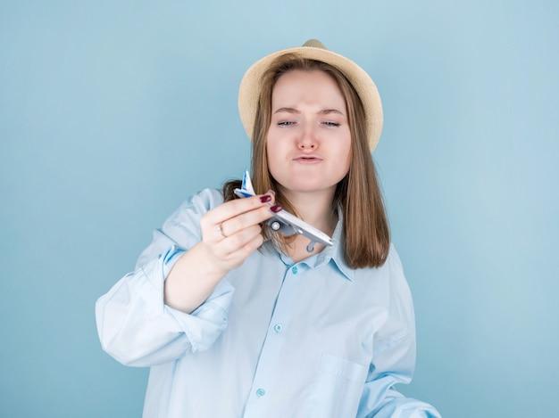 Donna turistica del viaggiatore in abiti casual estivi, cappello, aeroplano isolato sull'azzurro.