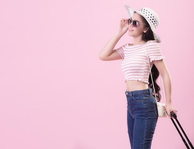 Donna turistica viaggiatore in abiti casual estivi. turisti che indossano cappelli, occhiali e trasportano bagagli con facce allegre e luminose su uno sfondo rosa.