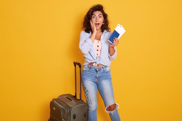 Donna turistica del viaggiatore che indossa abbigliamento casual che sta vicino alla sua valigia grigia