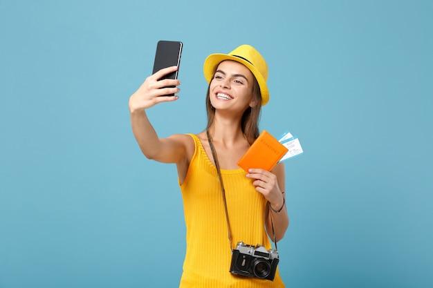 Donna turistica del viaggiatore in cappello giallo dell'abbigliamento casual che tiene selfie del cellulare dei biglietti su blue