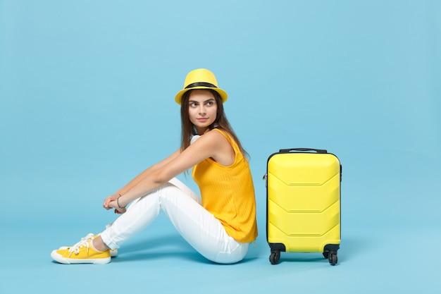 La donna turistica del viaggiatore in abiti casual estivi gialli, cappello si siede vicino alla valigia sul blu on