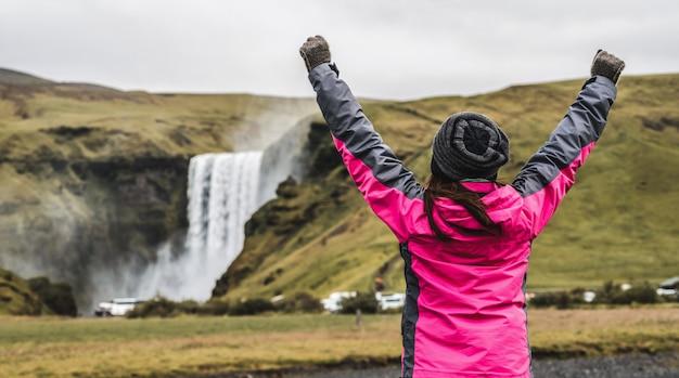 Viaggio del viaggiatore alla cascata di skogafoss in islanda.