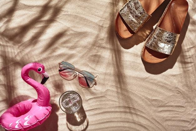 Gli accessori per le vacanze dei viaggiatori sono disposti su una vista piatta dall'alto di una spiaggia di sabbia bianca