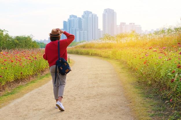 Un viaggiatore che cammina nel parco dei fiori fino all'edificio a seoul korea