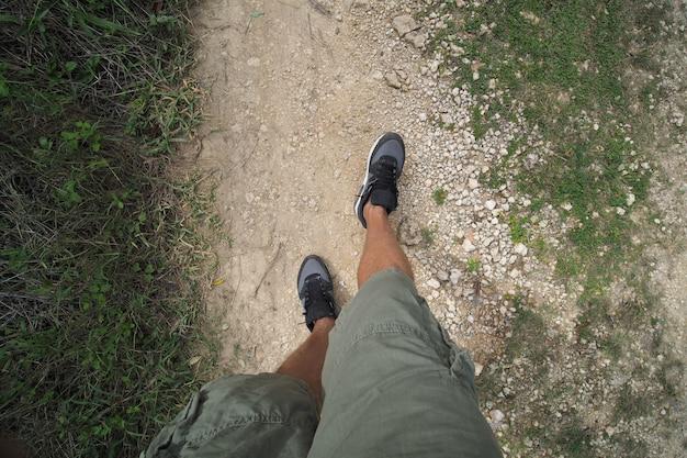 Viaggiatore che cammina alla strada rurale, pov.