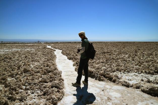 Viaggiatore che cammina sul sentiero del salar de atacama salt flat ad un'altitudine di 2305 m nel nord del cile