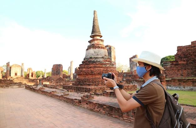 Viaggiatore che indossa la maschera per il viso a scattare foto durante la visita al tempio wat phra si sanphet in mezzo a covid19, ayutthaya, thailandia