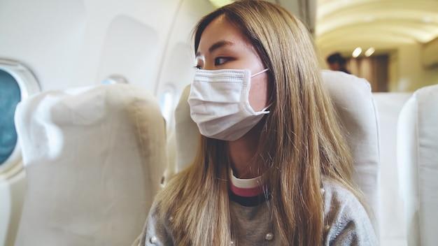 Viaggiatore che indossa la maschera facciale durante il viaggio in aereo commerciale.