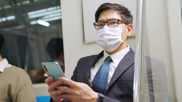 Viaggiatore che indossa la maschera per il viso mentre si utilizza il telefono cellulare sul treno pubblico