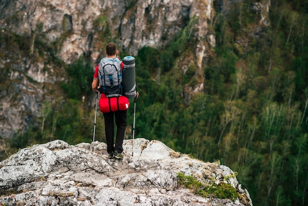 Un viaggiatore con uno zaino in montagna, vista posteriore. il concetto di uno stile di vita sportivo in viaggio. un uomo con uno zaino in montagna. escursioni in montagna. attività all'aperto. copia spazio