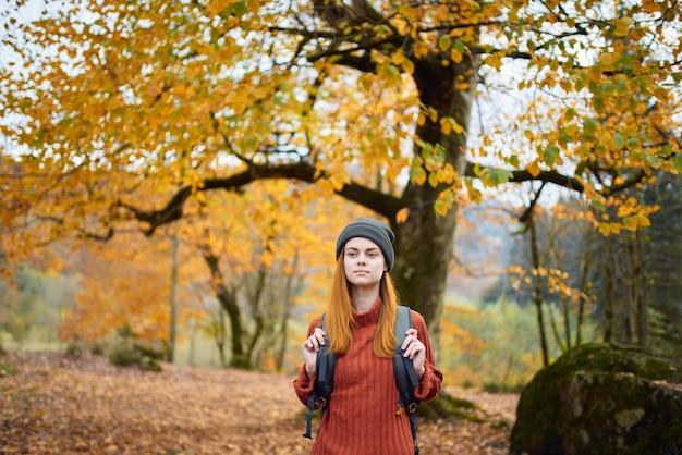 Viaggiatore con uno zaino che riposa nella foresta di autunno in natura vicino agli alberi