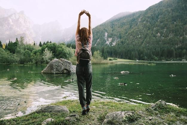 Viaggiatore a braccia alzate sulla natura con lago di fusine lago con monti mangart