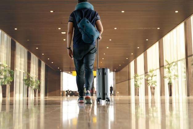 Viaggiatore con valigia che cammina con il trasporto di bagagli e passeggeri per tour nel terminal dell'aeroporto