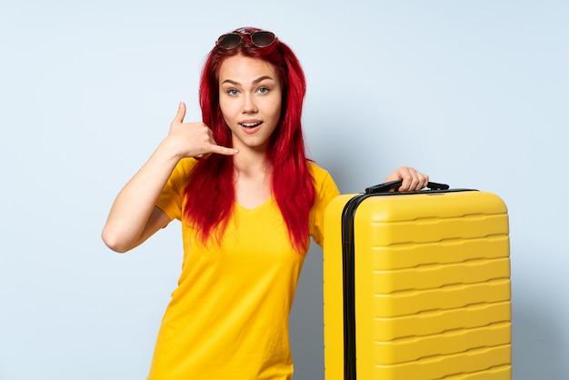 Donna del viaggiatore che giudica una valigia isolata sulla parete blu che fa gesto del telefono. richiamami segno