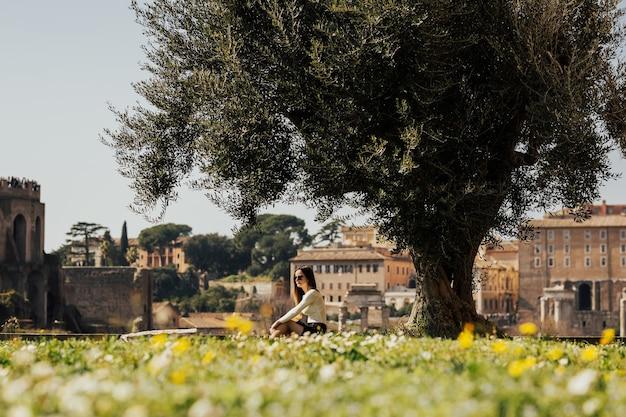 Donna del viaggiatore in posa accanto ai monumenti più importanti di roma, italia.