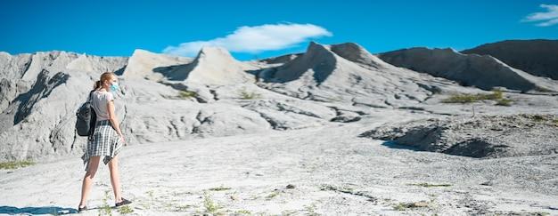 Donna del viaggiatore che cammina sulle montagne bianche