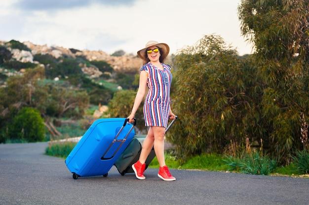 La donna viaggiatrice che indossa un vestito e un cappello si siede sulla valigia blu sulla strada e ride.