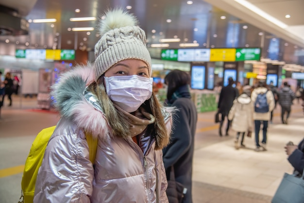 La donna del viaggiatore indossa una maschera medica per proteggere dal coronavirus presso la stazione di trasporto pubblico