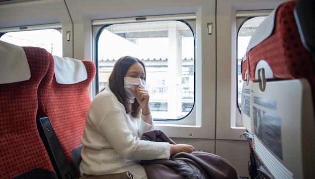 La donna del viaggiatore indossa una maschera medica per proteggere dal coronavirus nel treno di trasporto pubblico