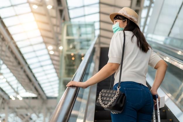 Donna viaggiatore con bagagli che indossa la maschera per il viso guardando fuori dal terminal in aeroporto in piedi sulla scala mobile