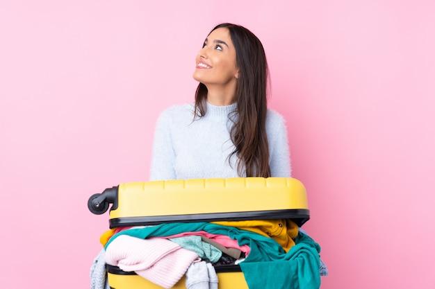 Donna del viaggiatore con una valigia piena di vestiti sopra la parete rosa isolata che ride e che cerca