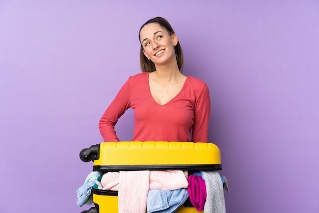 Donna del viaggiatore con una valigia piena di vestiti sopra la parete viola isolata che ride e che osserva in su