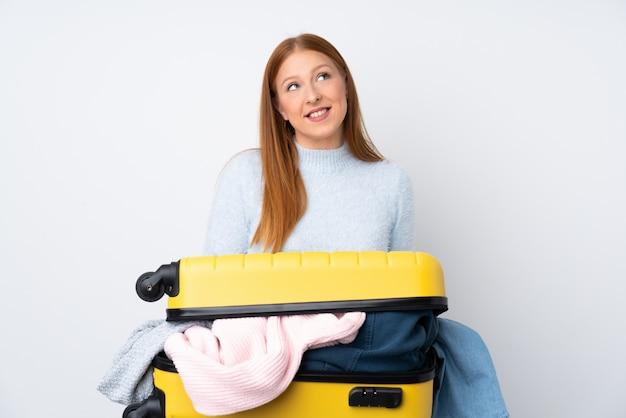 Donna del viaggiatore con una valigia piena di vestiti ridendo e guardando in alto
