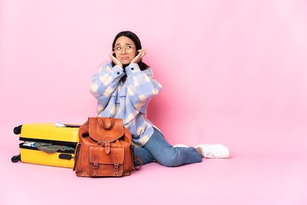 Donna del viaggiatore con una valigia che si siede sul pavimento frustrata e che copre le orecchie