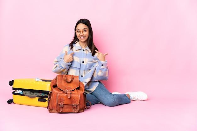 Donna del viaggiatore con una valigia che si siede sul pavimento che dà un pollice in alto gesto