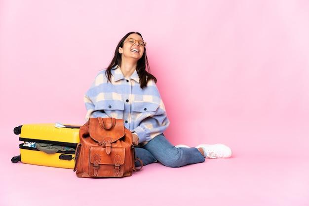 Donna del viaggiatore con una valigia che si siede sul pavimento che ride