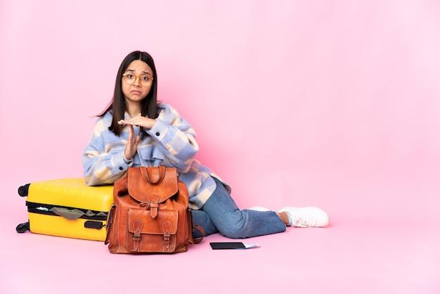 Donna del viaggiatore con una valigia che si siede sul pavimento che fa gesto di time out