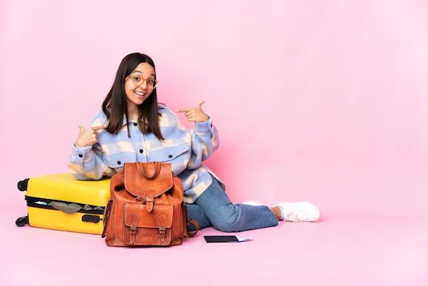 Donna viaggiatore con una valigia seduta sul pavimento orgogliosa e soddisfatta