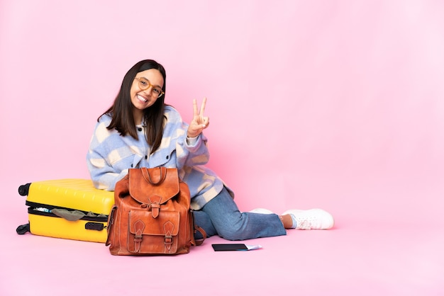 Donna del viaggiatore con una valigia che si siede sul pavimento che sorride e che mostra il segno di vittoria