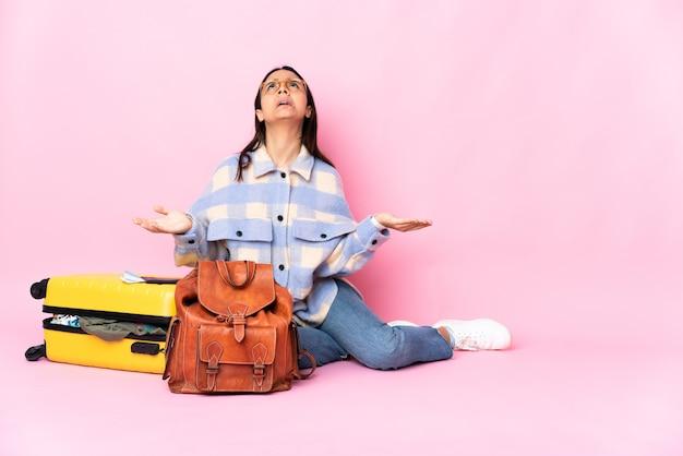 Donna del viaggiatore con una valigia che si siede sul pavimento ha sottolineato sopraffatto