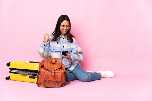 Donna del viaggiatore con una valigia seduta sul pavimento con il telefono in posizione di vittoria