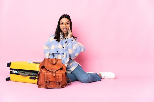 Donna del viaggiatore con una valigia che si siede sul pavimento con espressione facciale sorpresa e scioccata