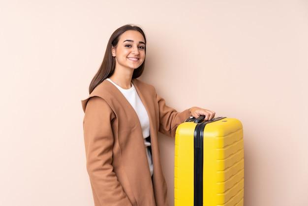 Donna del viaggiatore con la valigia che sorride molto