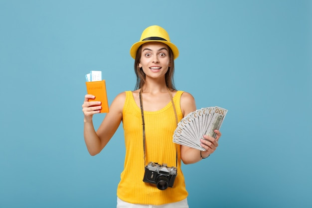 Donna viaggiatrice in abiti casual gialli e cappello che tiene la macchina fotografica dei soldi dei biglietti su blue
