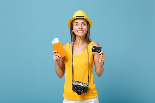 Donna del viaggiatore in cappello giallo dei vestiti che tiene la macchina fotografica della carta di credito dei biglietti su blue