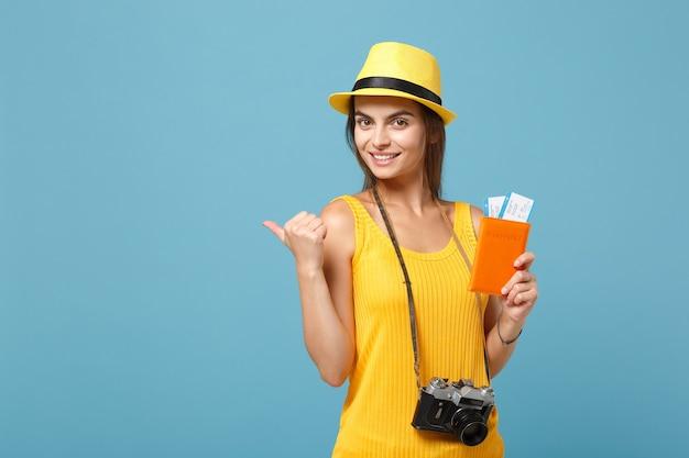 Donna viaggiatrice in abiti casual estivi gialli e cappello che tiene la macchina fotografica dei biglietti su blue