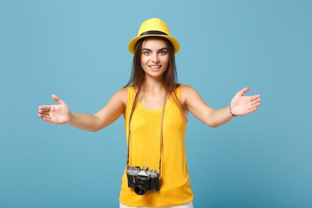 Donna viaggiatrice in abiti casual estivi gialli e cappello con macchina fotografica su blu