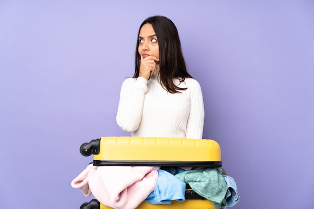 Giovane donna del viaggiatore con una valigia piena di vestiti isolata