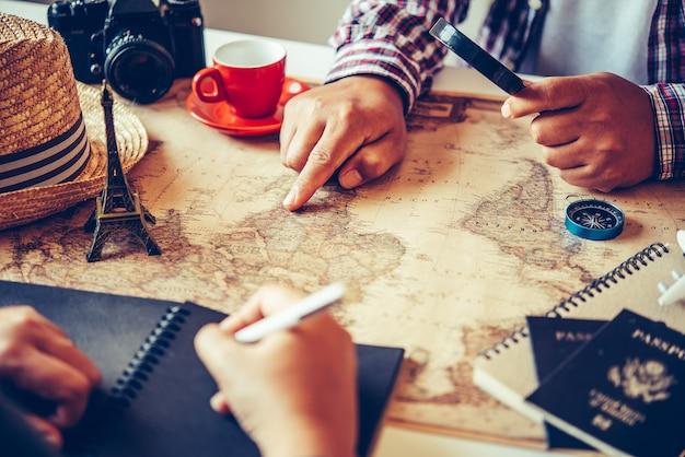I viaggiatori stanno pianificando un viaggio cercando il percorso sulla mappa e cercando informazioni su internet.