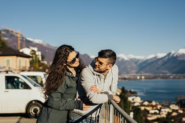 Le coppie di viaggiatori si guardano vicino alla montagna e al lago innevati.